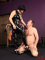 Femdom-goddess Julie Spanks has her villein bent over on his hands and knees exposing his balls for easy access castigation. ....