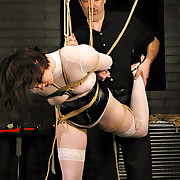 Tied up and suspended girl in corset