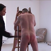 Two naked chaps strapped visciously across their well striated butocks by vulgar miss