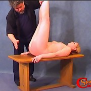 Pretty chick has her butt spanked lying on the table