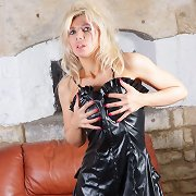 Blonde tease Nicole bows over in her leather costume and flashes her pussy