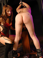 Restrained slave takes some nasty ass-whipping from a beautiful mistress in top-boots