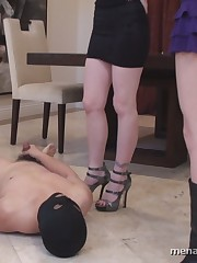 Stroking slave lying on the floor in front of Mistresses