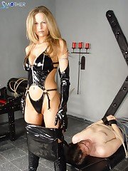 Mistress in latex sat at the slave's face.