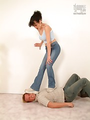Brunette mistress stands on man's face.