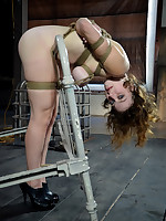 Submissive girl tied to bed frame, suspended over mattress