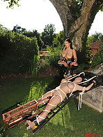 Big-breasted Domme ties down equally busty girl outdoors