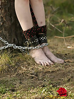 Helpless brunette naked, gagged and chained to a tree