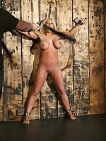 Hooded slavegirl subjected to tit torture