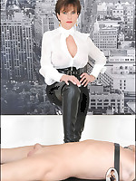 Domme in tall boots teases slaveboy on bed