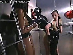 Two Dommes spank a slave in latex.