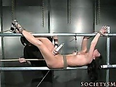 Slavegirl restrained inside a confining metal cube.