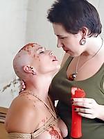Bald beauty in bondage endures hot wax and spanking
