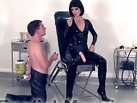 Latex mistress shows her strapon to a slave
