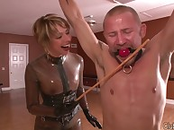 Latex milf castigating a gagged slave