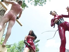Two brutal Dominatrixes in latex were whipping slave