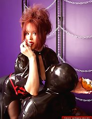 Hot mistress in rubber dress plays and teases her rubber slave in dungeon