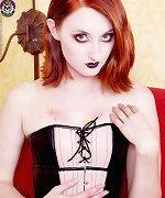 Hot punk in tight corset dress pierces her flesh