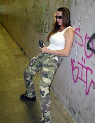 Posing down a dark alley in camo with massive strapon
