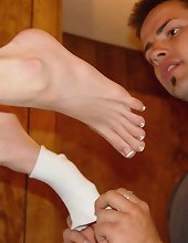 A happy boy removed mistress` socks and kissed her toes