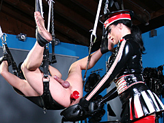 A subject is fixed to a love swing in her fully equipped SM studio