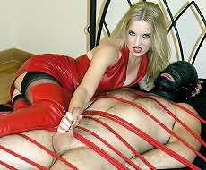 Mistress in red leather sat on slave and tugged his cock