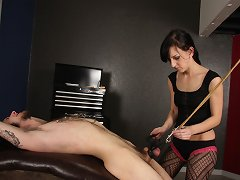 Elise Graves has her slave bent over backwards and attaches heavy weights on a pulley to her slave\'s balls.